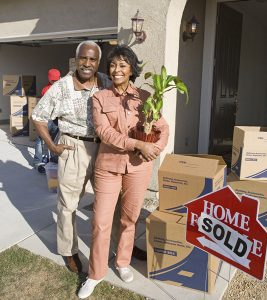 Couple smiling outside the home they've just sold surrounded by moving boxes.