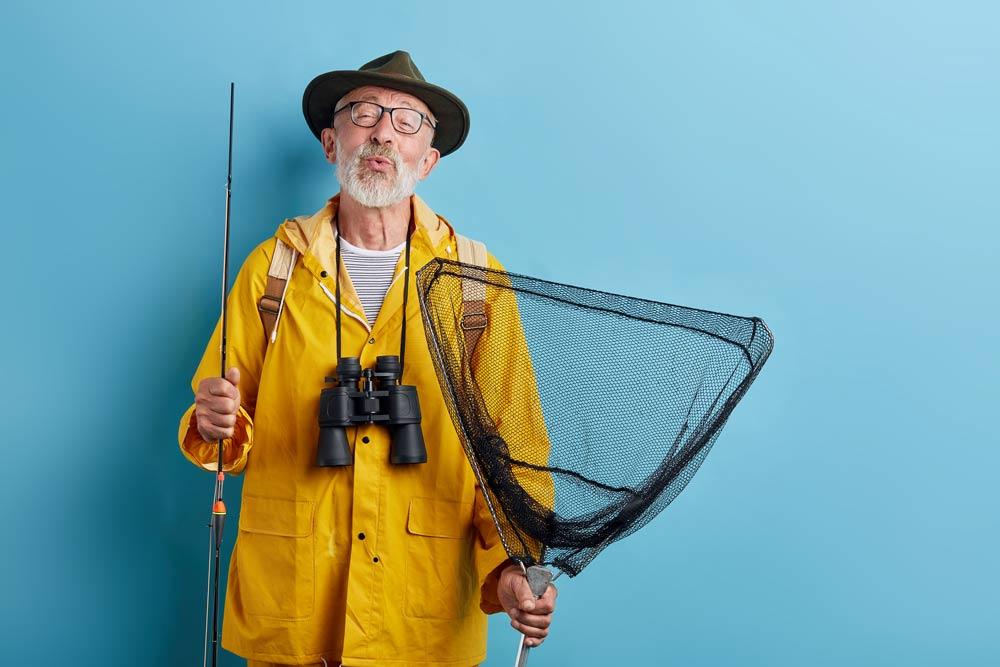 man standing against blue background with fishing equipment, rain coat, and binoculars.