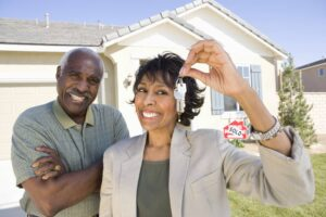 Smiling couple in front of newly purchased home