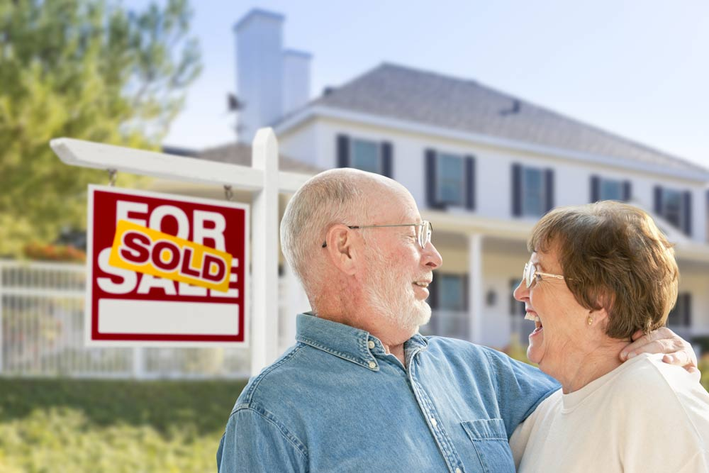 Happy couple standing in front of House Sold sign.
